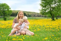 Happy Mother and Young Children Relaxing in Flower Meadow Stock Photo