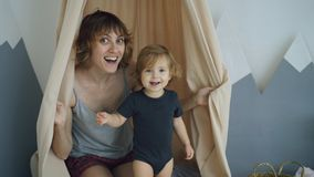 Happy mother with young cute daughter playing and and hide behind curtain at home. In the morning Stock Image