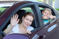 Happy mother and young daughter waving from car Stock Photo