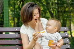 Happy motherhood: cheerful infant playing with mother sitting on her knees in park. Mom is feeding kid with puree on spoon royalty free stock photos