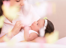 Happy motherhood concept. Cute young mother looking on sweet newborn daughter, take care about her, photo with soft focus, happy motherhood concept royalty free stock photo