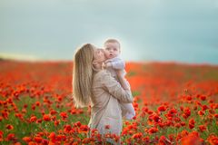 Happy motherhood. Mom and son daughter are playing in the field of flowering red poppies stock image