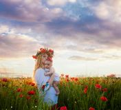 Inspired young mother. Happy motherhood in the poppy field on a sunset. Inspired nature landscape with people. Mom with her baby Stock Photos