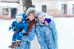 Happy mothers and babys playing on snow Royalty Free Stock Photos