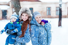 Happy mothers and babys playing on snow Stock Photography