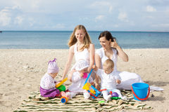 Happy mothers with children at the beach Royalty Free Stock Images