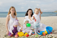 Happy mothers with children at the beach Royalty Free Stock Image