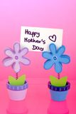 Happy Mothers Day. Two paper clips made from flowers with Mothers Day wishes on a pink reflective background Royalty Free Stock Photos