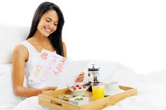 Happy mothers day. Breakfast in bed mum is happy and smiling, reading a card in the morning royalty free stock photos