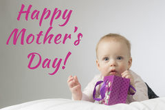 Happy mothers day. Adorable little baby lying on the white blanket and holding purple gift bag in his hands. Horisontal studio sho. Adorable little baby lying on Royalty Free Stock Images