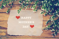 Happy Mothers day on brown paper with white flower on wooden Royalty Free Stock Images
