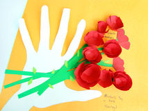 Happy Mothers Day card. Red roses on card - A bright and cheerful card for greetings on Happy Mothers Day. Hand holding a bunch of red roses with fresh green royalty free stock image
