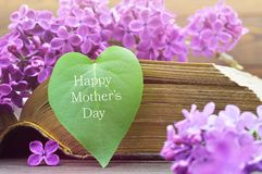 Happy Mothers Day card. With heart shaped leaf and lilac flowers stock images