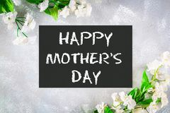 Happy mothers day. A chalkboard is surrounded by white flowers on a gray background. stock photo
