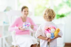 Happy mothers day. Child with present for mom. Happy Mothers Day. Child with present and flowers for mom. Little boy holding wrapped gift and flower bouquet for stock image