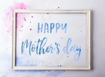 Happy mothers day composition. A text in a wooden frame on white background. Studio shot. Royalty Free Stock Image