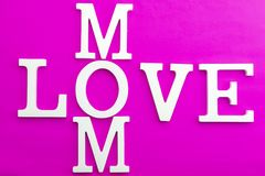 Happy mothers day concept,Love mom wooden text on pink paper background stock photo