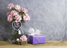 Happy mothers day concept of pink carnation flowers in bottle. With i love mom letter on heart wood and violet gift box royalty free stock photo
