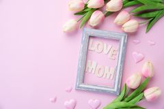 Happy mothers day concept. pink tulip flower with paper heart and Picture Frame with LOVE MOM text on pink pastel background.  royalty free stock images