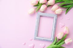 Happy mothers day concept. pink tulip flower with paper heart and Picture Frame with LOVE MOM text on pink pastel background.  royalty free stock photography