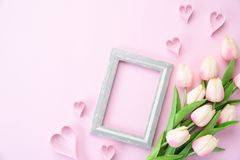 Happy mothers day concept. pink tulip flower with paper heart and Picture Frame with Happy mother`s day text on pink pastel. Background stock photo