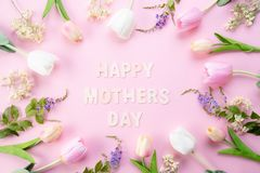 Happy mothers day concept. Top view of pink tulip flowers in frame with happy mothers day text on pink pastel background. Flat lay royalty free stock photos