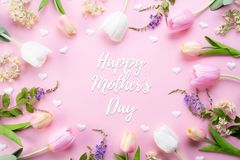Happy mothers day concept. Top view of pink tulip flowers in frame with happy mother`s day text on pink pastel background. Flat. Lay stock photography