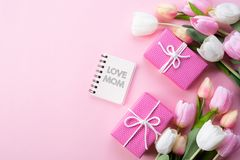 Happy mothers day concept. Top view of pink tulip flowers, gift box and note book with LOVE MOM text on pink pastel background. stock images