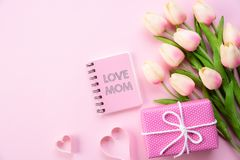 Happy mothers day concept. Top view of pink tulip flowers, gift box and note book with LOVE MOM text on pink pastel background. stock photo