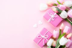 Happy mothers day concept. Top view of pink tulip flowers, gift box on pink pastel background. Flat lay royalty free stock photos