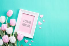 Happy mothers day concept. Top view of pink tulip flowers and white picture frame with LOVE MOM text on green pastel background. Flat lay stock photography