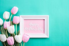 Happy mothers day concept. Top view of pink tulip flowers and white picture frame with happy mother`s day text on green pastel. Background. Flat lay royalty free stock images