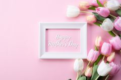 Happy mothers day concept. Top view of pink tulip flowers and white picture frame with happy mothers day text on pink pastel. Background. Flat lay royalty free stock image