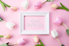 Happy mothers day concept. Top view of pink tulip flowers and white picture frame with happy mothers day text on pink pastel royalty free stock image