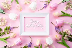 Happy mothers day concept. Top view of pink tulip flowers and white picture frame with happy mothers day text on pink pastel. Background. Flat lay stock photography