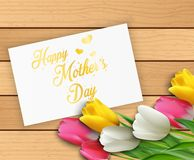 Happy Mothers Day with flowers tulips and paper on wooden background Royalty Free Stock Photos