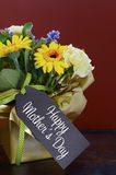 Happy Mothers Day gift of Spring Flowers on dark wood table. Royalty Free Stock Photo