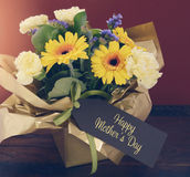 Happy Mothers Day gift of Spring Flowers on dark wood table. Royalty Free Stock Photos