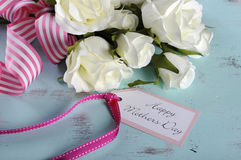 Happy Mothers Day gift of white roses bouquet with pink stripe ribbon and gift tag Stock Photo