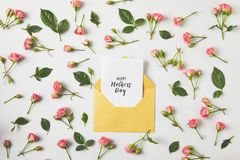 Happy mothers day greeting card in envelope and beautiful pink roses and green leaves on grey royalty free stock photos