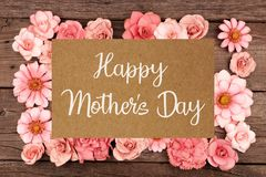 Happy Mothers Day greeting card with frame of pink paper flowers over wood