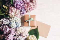 Happy mothers day greeting card mockup. International Women`s day. Beautiful hydrangea flowers, gift box and paper greeting card. On rustic white wood, flat lay royalty free stock images