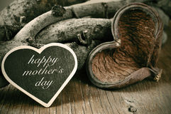 Happy mothers day in a heart-shaped chalkboard on a rustic backg. A heart-shaped chalkboard with the text happy mothers day written in it and a heart-shaped Stock Photos