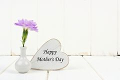 Happy Mothers Day heart tag with carnation against white wood Stock Photography