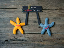 Happy mothers day, i love you mom. Happy mothers day with i love you mom message, idea from colorful fabric starfish on wooden background, abstract wooden royalty free stock images