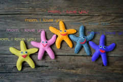 Happy mothers day, i love you mom. Happy mothers day with i love you mom message, idea from colorful fabric starfish on wooden background, abstract wooden stock images