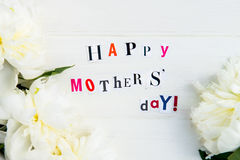 Happy Mothers Day Letters Cut out from Magazines and White Peonies stock photos