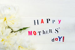Happy Mothers Day Letters Cut out from Magazines and White Peonies stock photography