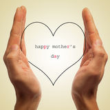 Happy mothers day. Man hands holding a silhouette of a heart with the sentence happy mothers day written in it Royalty Free Stock Photography