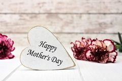 Happy Mothers Day message on rustic wood heart with flowers Stock Photo